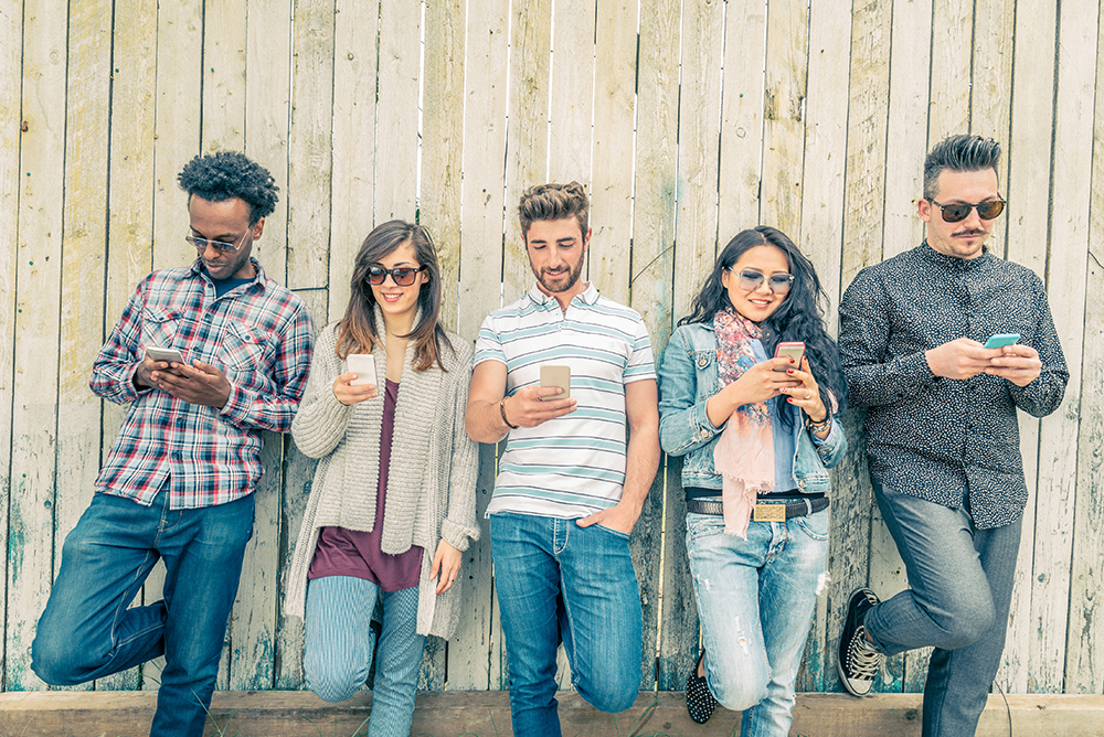 People leaning up against a fence looking at their smart phones. Here are some tips on how to seek and reward quality content. People have the right to encourage quality through conscious choice.